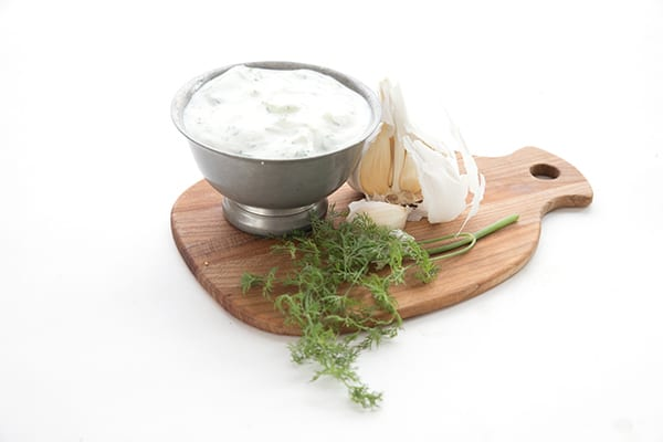 Garlic and dill on a cutting board with tzatziki sauce