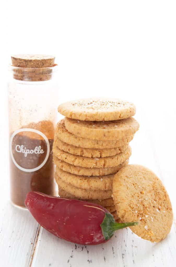 A stack of keto chipotle cheese crisps with a red jalapeno and a jar of chipotle powder.