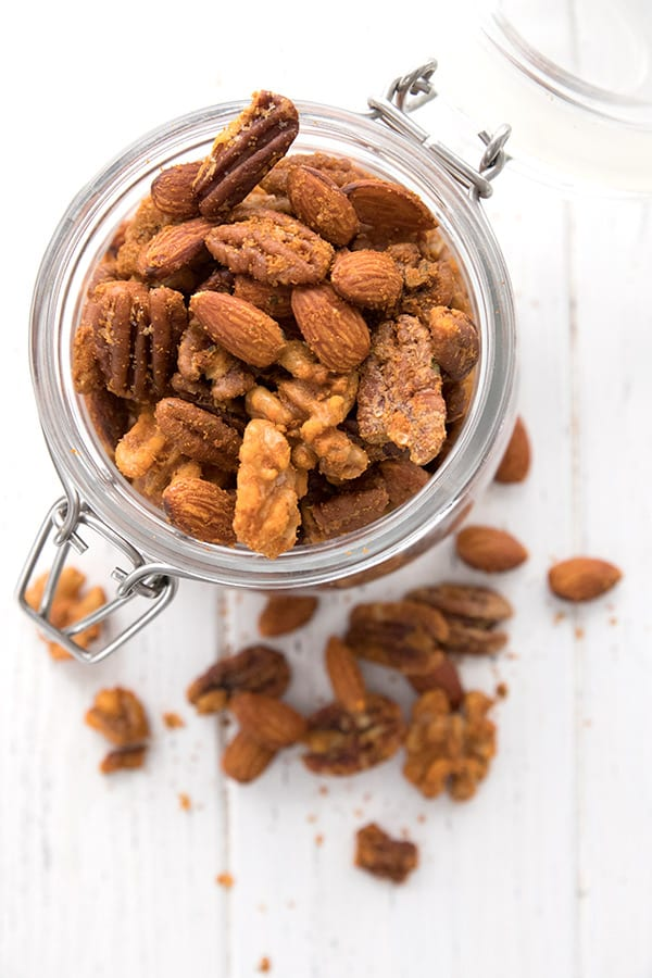 Top down photo of a jar of keto roasted nuts with a few nuts scattered around, on a white wooden table.