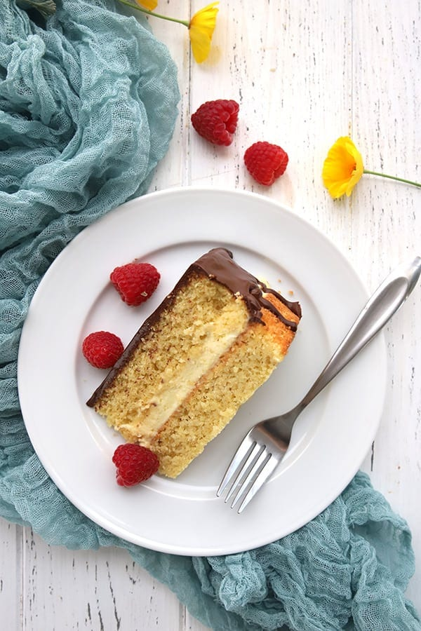 Top down photo of a slice of low carb Boston Cream Pie on a white table, with a fork and raspberries