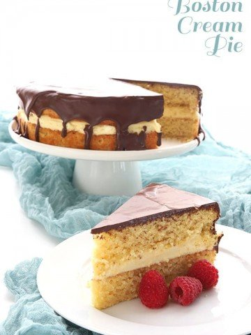 Keto Boston Cream Pie recipe - a slice of the cake on white plate with raspberries, with the rest of the cake on a white cake stand in the background