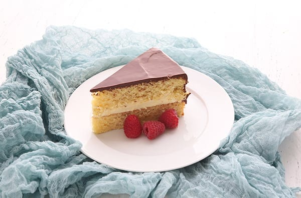 Single slice of Boston Cream Pie on a white plate with raspberries, surrounded by teal gauzy fabric