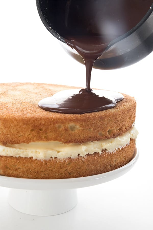 Sugar free chocolate ganache being poured over a low carb Boston Cream Pie