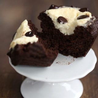 A keto chocolate cream cheese muffin on a cupcake stand, cut open to see the inside.