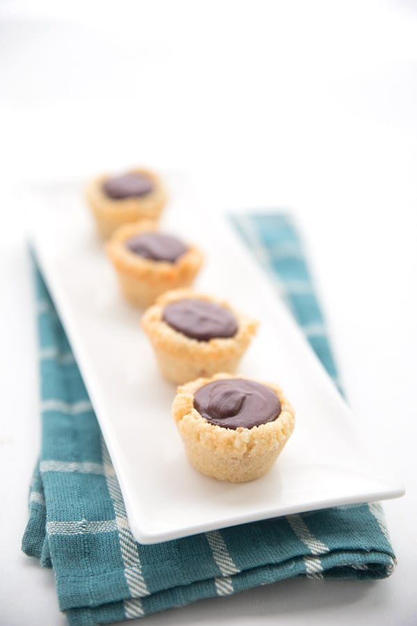 Keto Chocolate Macadamia Tarts on a white platter