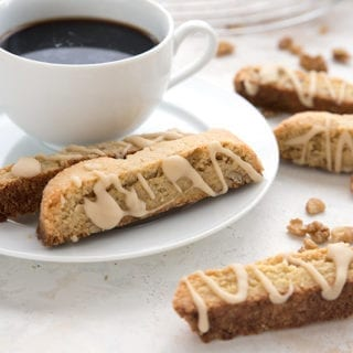 A cup of coffee with two keto biscotti on the saucer and one in front