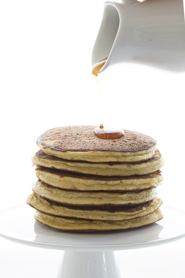 maple syrup being poured over a stack of keto pancakes made with coconut flour