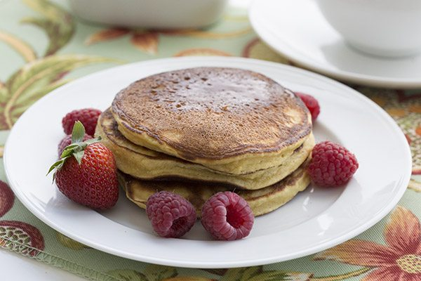 round white plate with a short stack of grain free pancakes and fresh berries