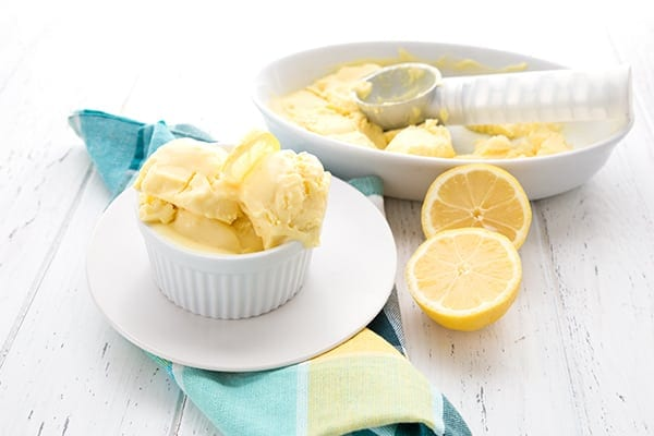Low Carb Lemon Ice Cream in a white bowl with lemon halves around it