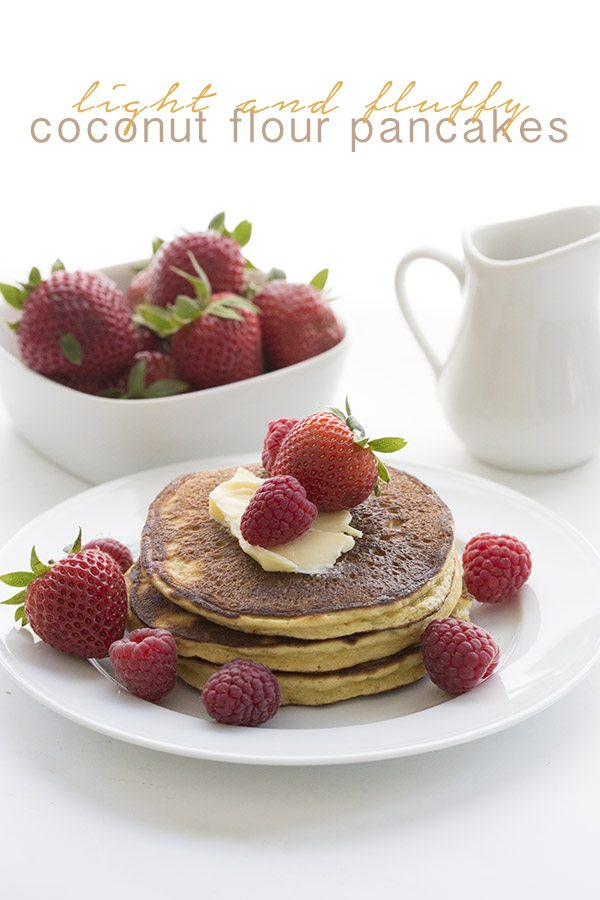 titled image - light and fluffy coconut flour pancakes - a stack of keto pancakes sits on a plate topped with butter and fresh strawberries