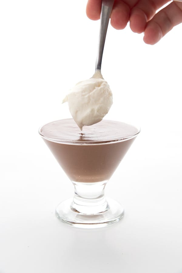 Easy sugar-free pudding with coconut milk in a dessert cup with whipped cream being dolloped on top