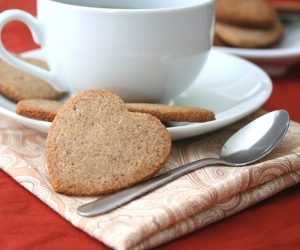 heart shaped homemade Biscoff cookies next to a white mug of coffee