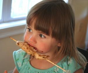 A little girl eating a Goddess Chicken Satay