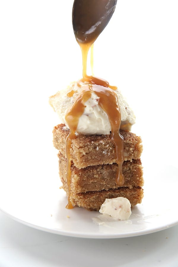 Drizzling sugar free caramel sauce over a stack of snickerdoodle blondies with some ice cream on top.