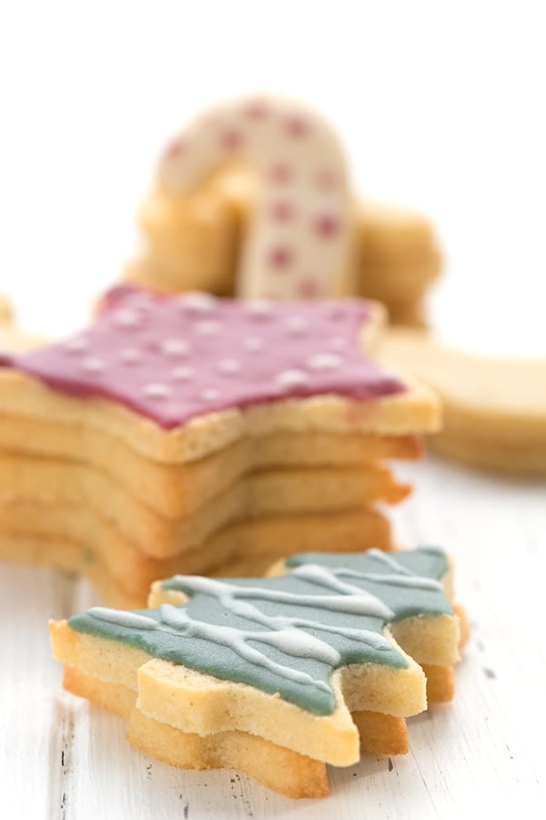 Perfect keto cut out sugar cookies in stacks on a white table.