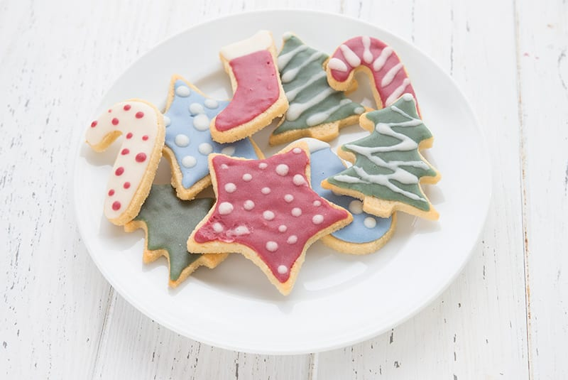 Keto sugar cookies on a white plate, all decorated with holiday colors and designs