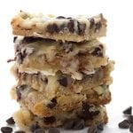 Low Carb Magic Cookie Bars in a stack with chocolate chips around them.
