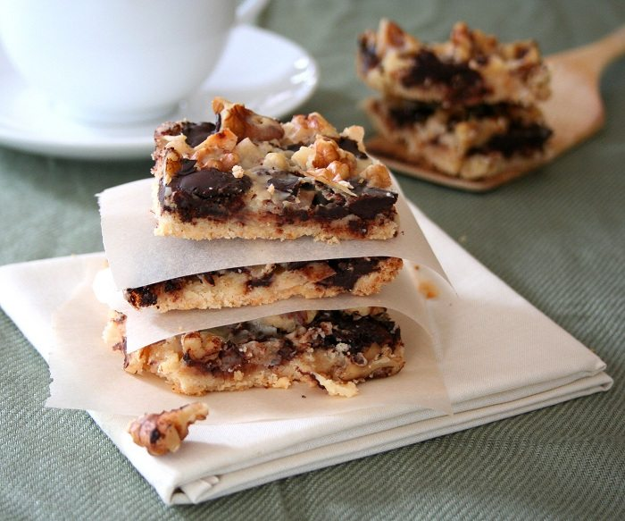 three Sugar Free Magic Cookie Bars stacked on a linen napkin