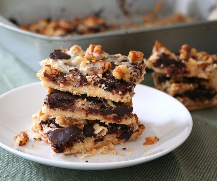 gluten-free magic cookie bars stacked on a white dessert plate