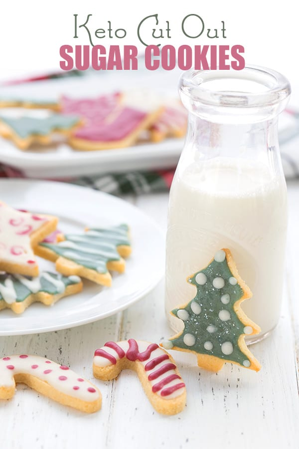 Keto sugar cookies on a white table with a bottle of milk. More sugar cookies in the background, all decorated with sugar-free royal icing