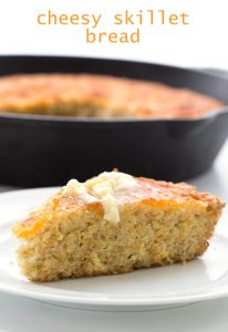 titled image (and shown): Cheesy Skillet Bread (a slice of low carb skillet bread on a plate, topped with butter)