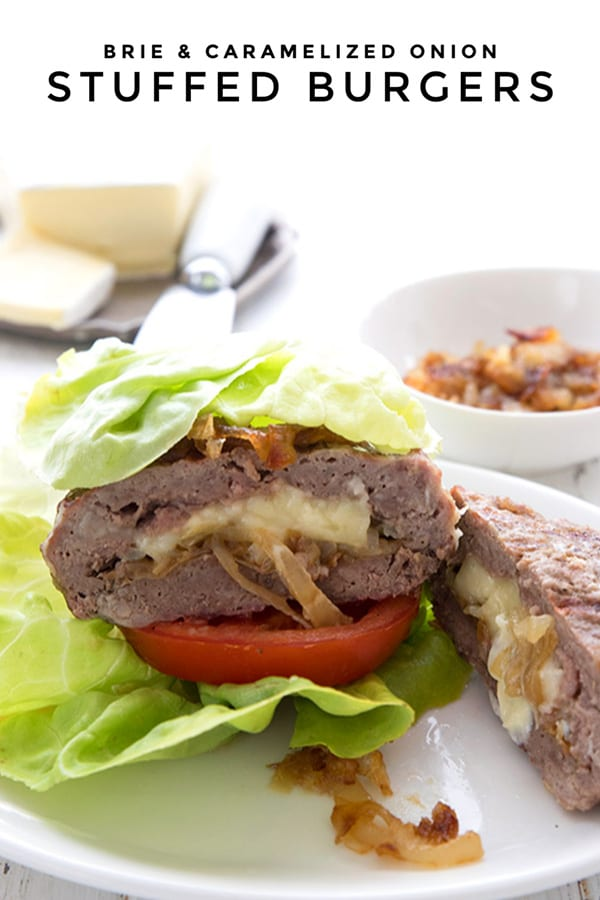 A keto stuffed burger in a lettuce wrap on a white plate, with brie and caramelized onions in the background.