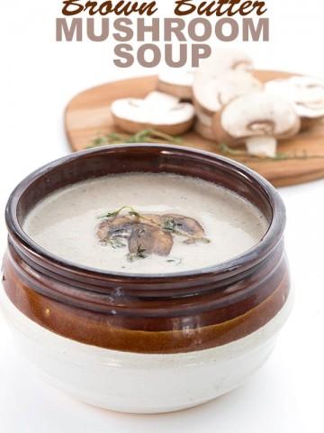 Keto Mushroom Soup in a brown bowl with sliced mushrooms in behind.