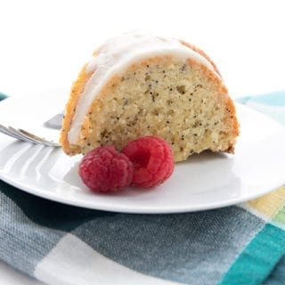A slice of low carb lemon poppyseed cake on a white plate with a plaid napkin