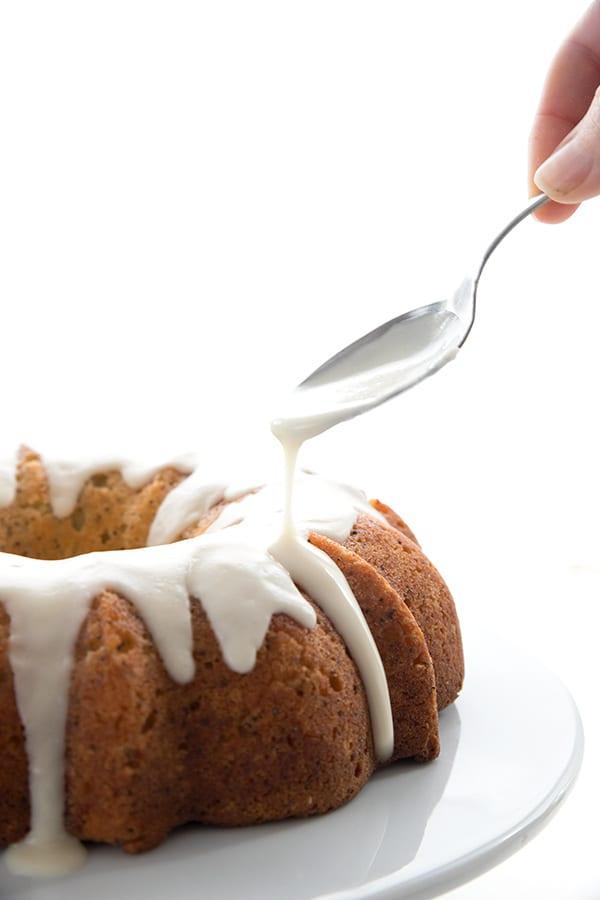 Drizzling lemon glaze over lemon poppy seed cake