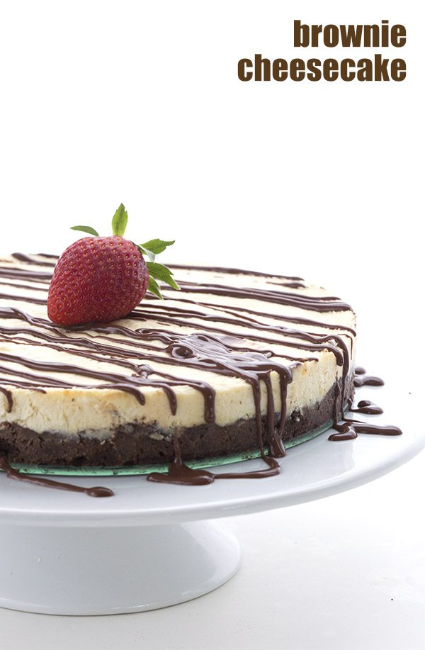 Low Carb and Gluten-Free brownie cheesecake drizzled with sugar free chocolate sauce sitting on a white cake stand