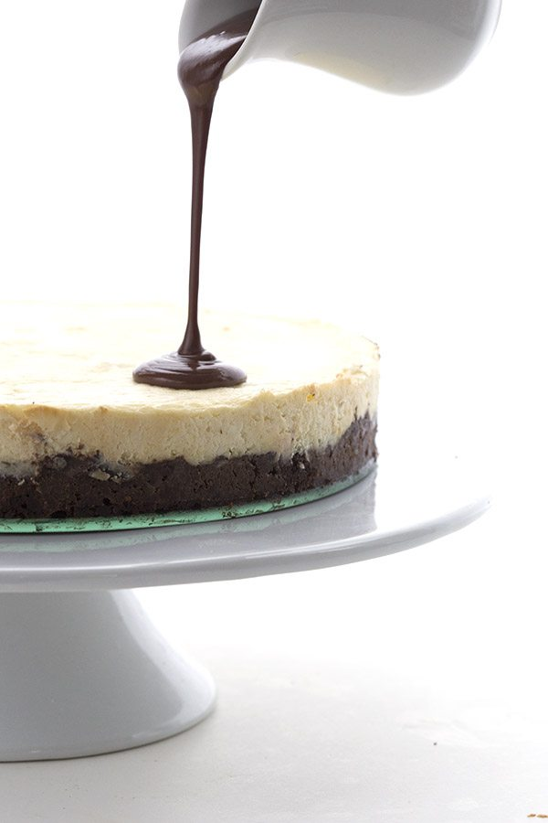 sugar-free chocolate ganache being poured over the top of a keto Brownie Cheesecake