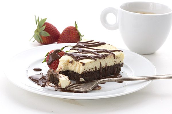 slice of gluten-free Brownie Cheesecake on a white dessert plate. A forkful of cheesecake sits on the plate.