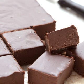 Squares of keto fudge on a white table with a knife in the background