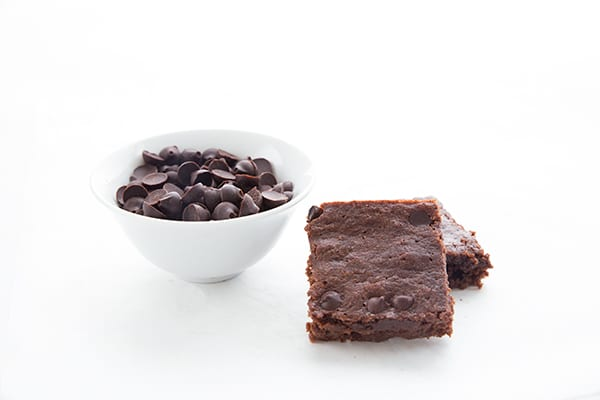 A small bowl of sugar-free chocolate chips with two low carb brownies