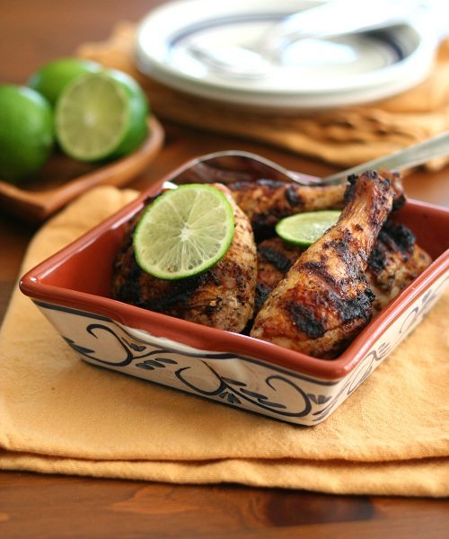serving dish filled with grilled chipotle lime chicken topped with fresh lime slices