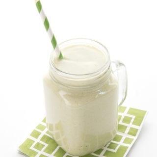 Creamy avocado smoothie in a large glass mug