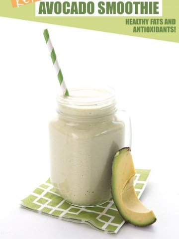 Healthy avocado smoothie in a glass with a slice of avocado and a green stripped straw