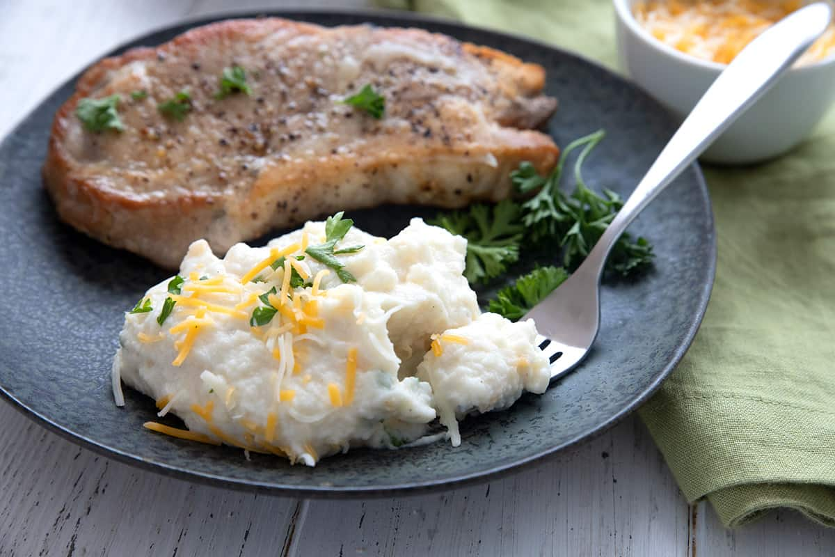 A fork digging into a mound of creamy cauliflower mashed potatoes on a black plate.