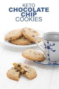 Keto chocolate chip cookies on a plate with a cup of coffee and one cookie broken