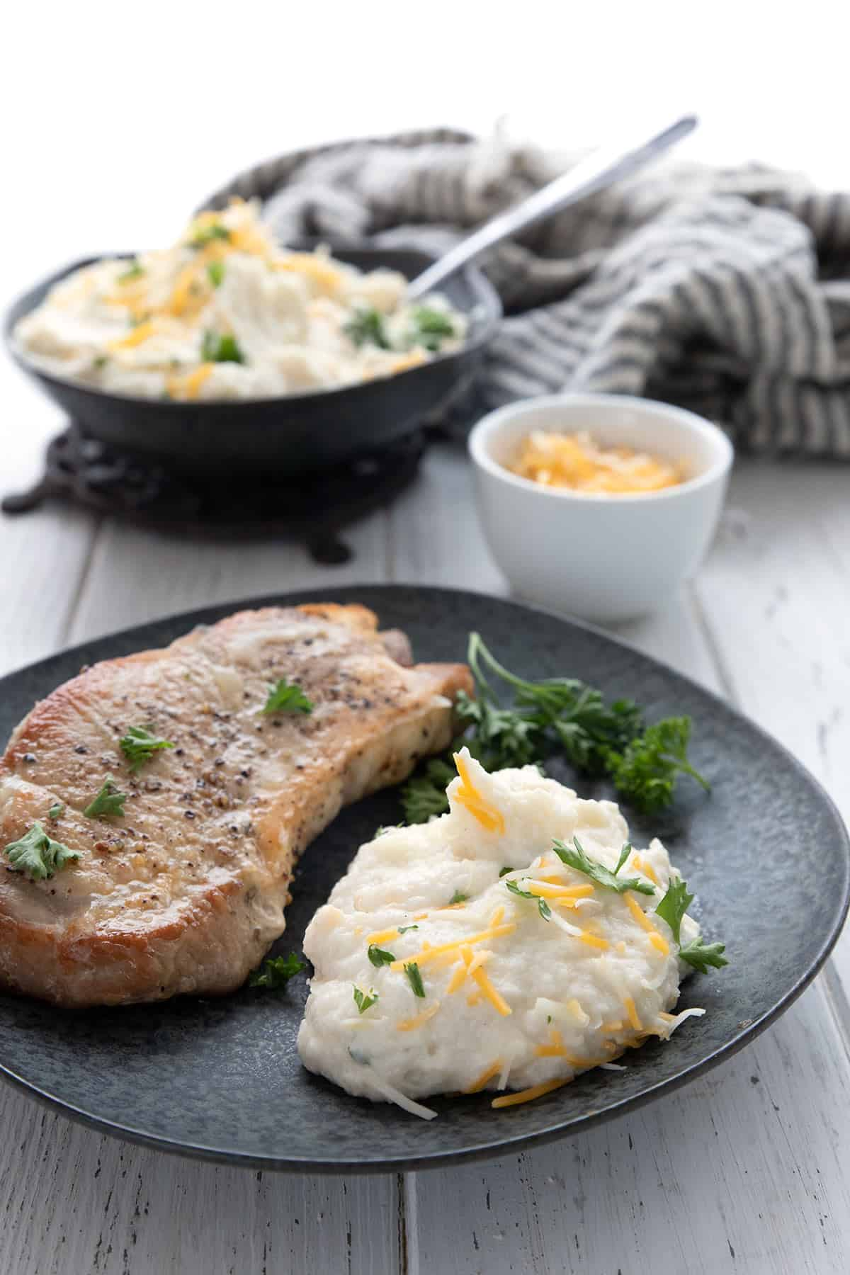 A black plate with a pork chop and a dollop of keto mashed cauliflower on a white table.
