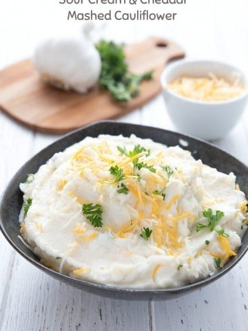 Titled image of keto mashed cauliflower in a black bowl, topped with cheddar and parsley.