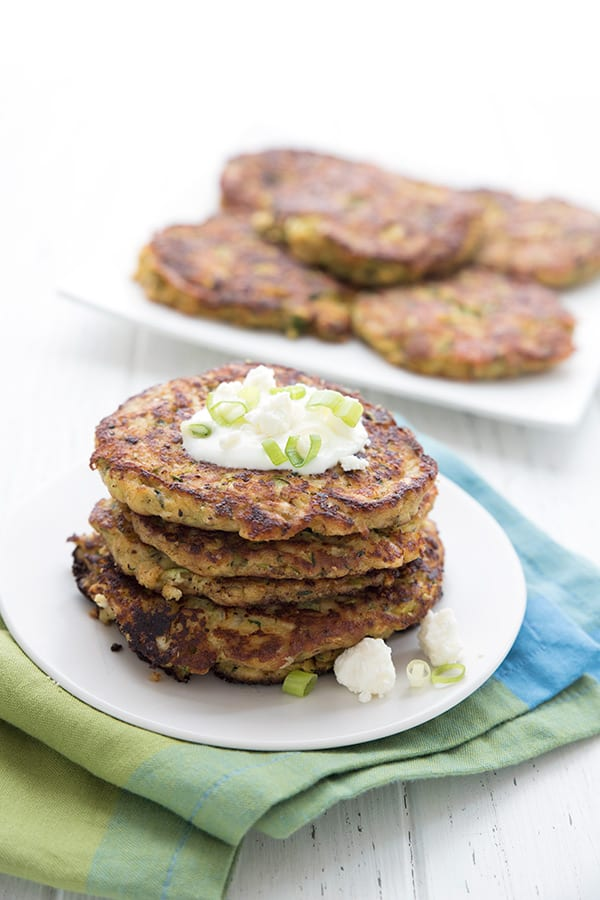 A stack of zucchini fritters with a platter full of them in the background