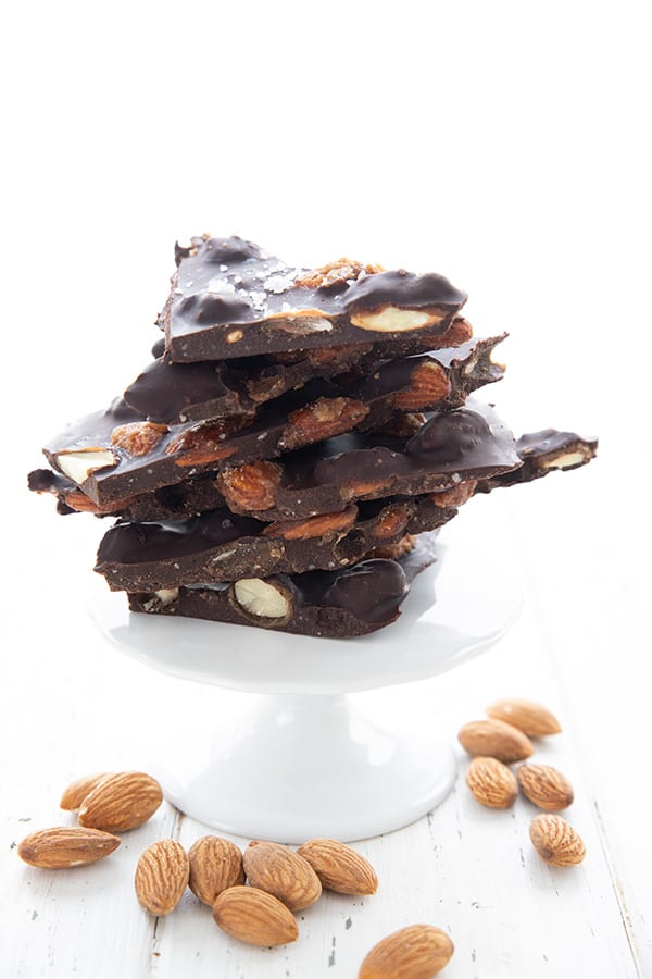Keto almond bark on a white cake stand with almonds strewn around.