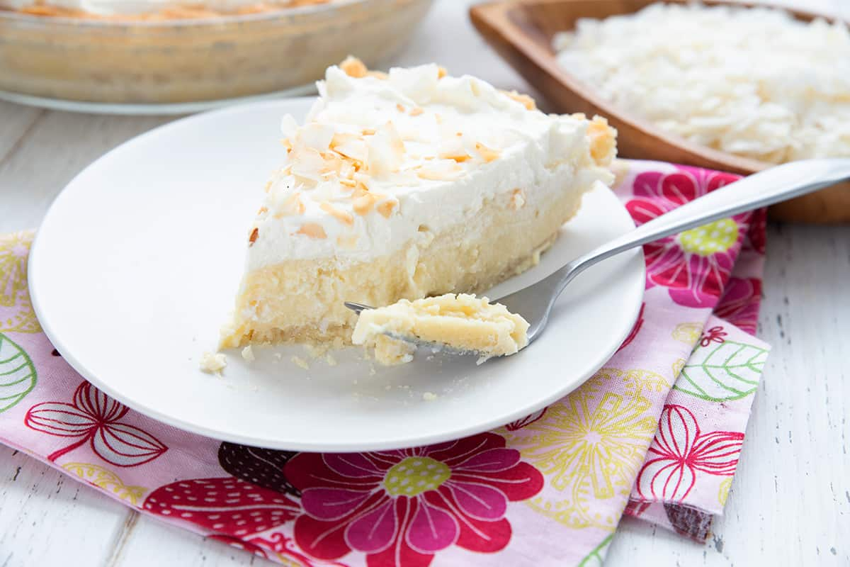 A slice of coconut cream pie over a floral pink napkin, with a forkful taken out of the pie.