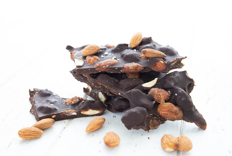 Pieces of keto chocolate almond bark in a small pile with almonds around it.