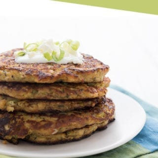 A stack of keto zucchini fritters on a white plate with a green and blue napkin
