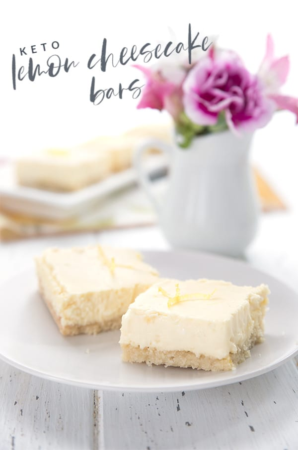 Keto lemon cheesecake bars on a white plate with a vase of flowers in the background.