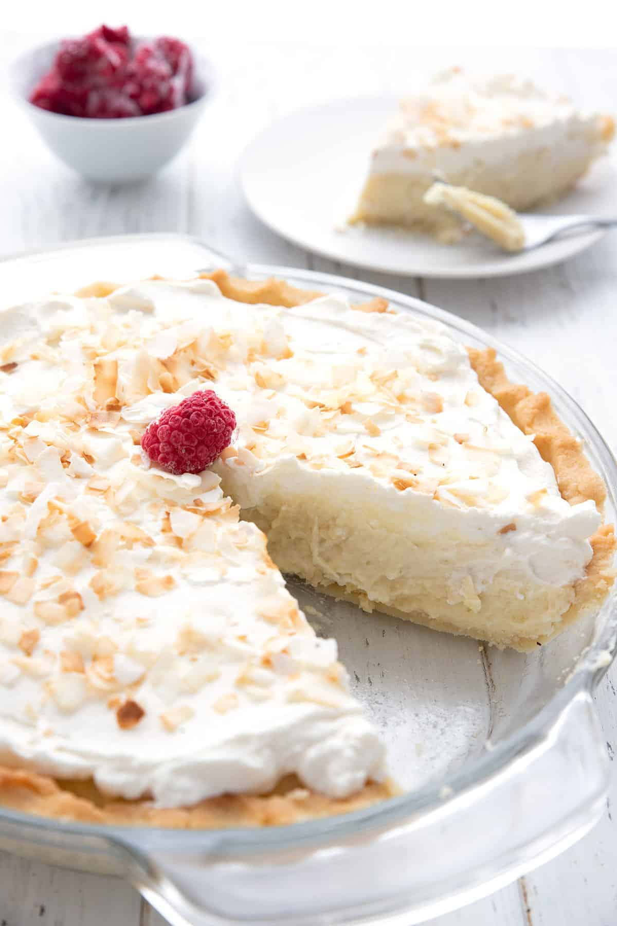 A sugar free coconut cream pie with a slice taken out of it.