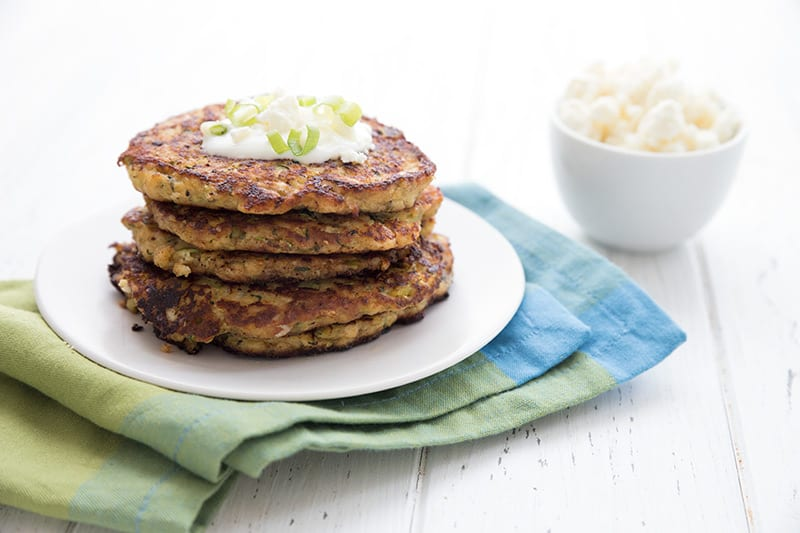 Zucchini fritters with feta and green onion in a stack on a white plate