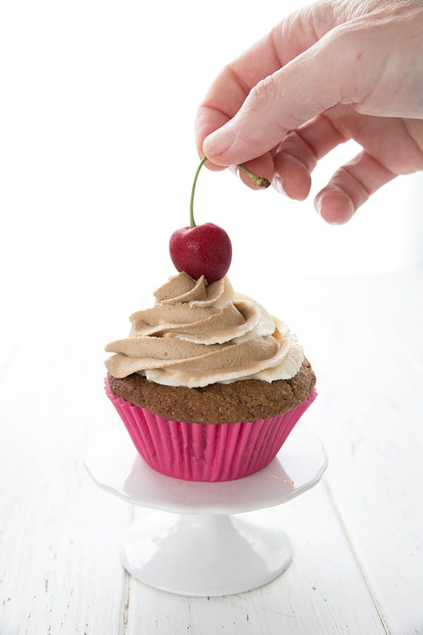 A hand placing a cherry on top of a root beer cupcake.